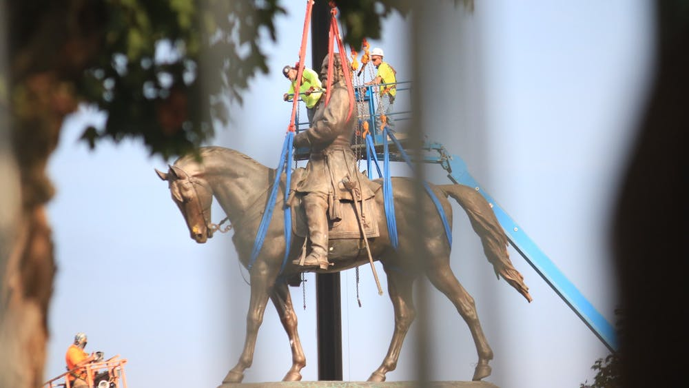 Harnesses are attached to the Robert E. Lee statue to before being lifted off of its stand.