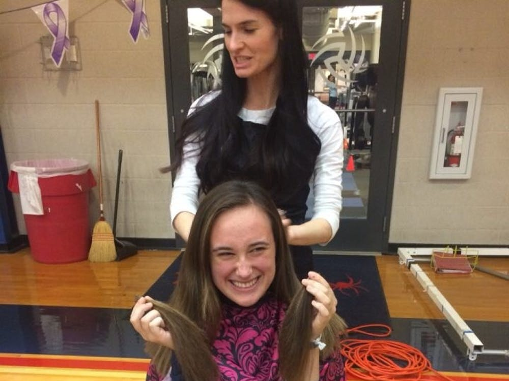 Freshman Carly Green donates her hair at the Pantene Beautiful lengths station.