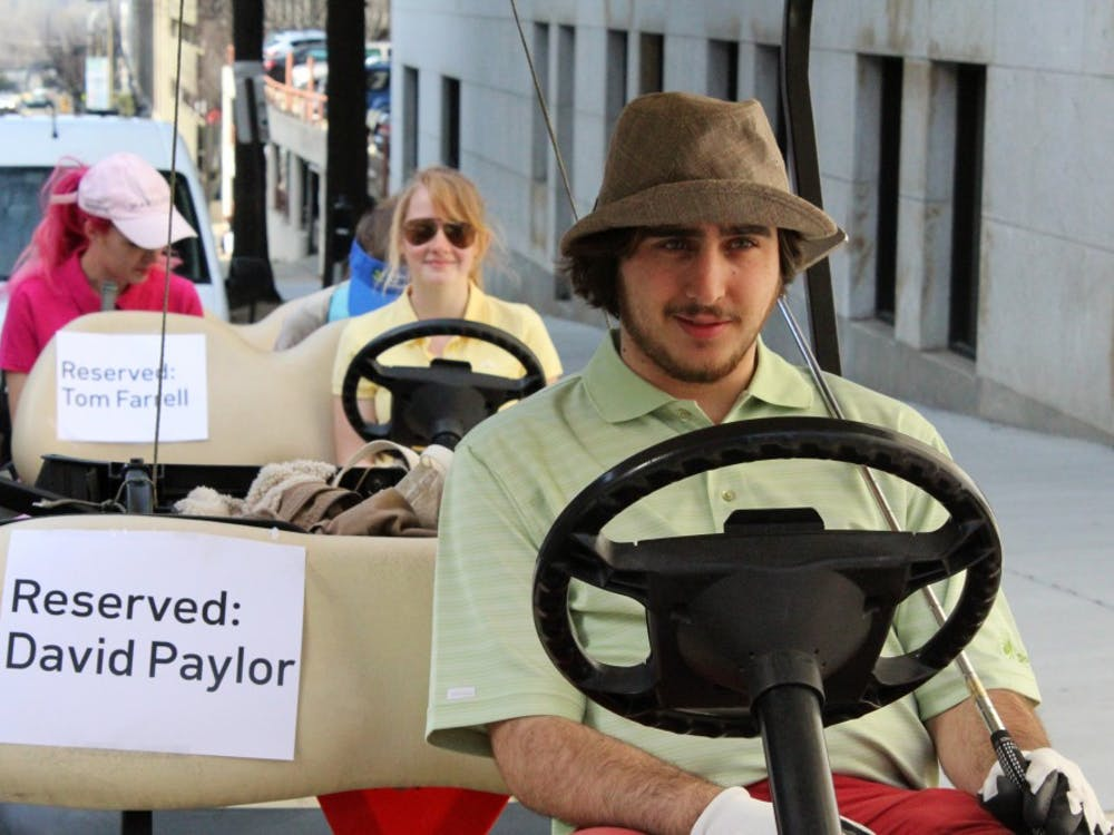 Michael James-Deramo, chair of the VCU chapter of the Virginia Student Environmental Coalition, sits in a golf cart meant to represent the Masters tournament trip gifted to David Paylor by Dominion in 2013.