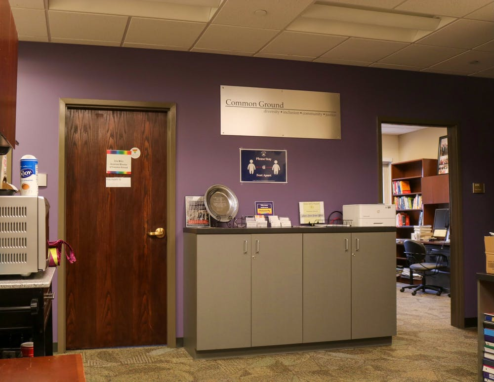 <p>The sign denoting the Office of Common Ground stands out amongst a sea of purple paint.</p>