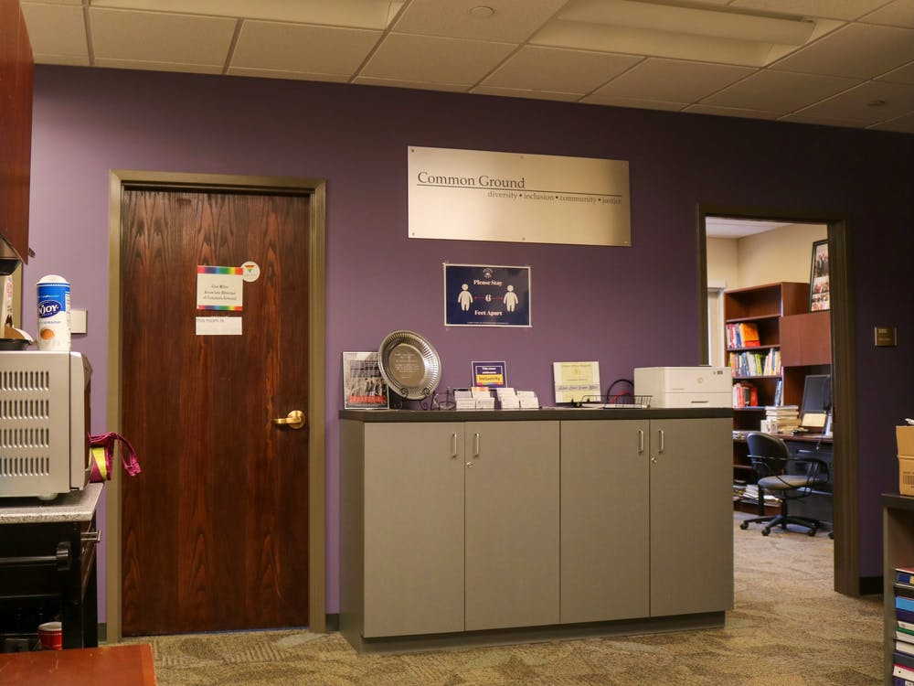 The sign denoting the Office of Common Ground stands out amongst a sea of purple paint.