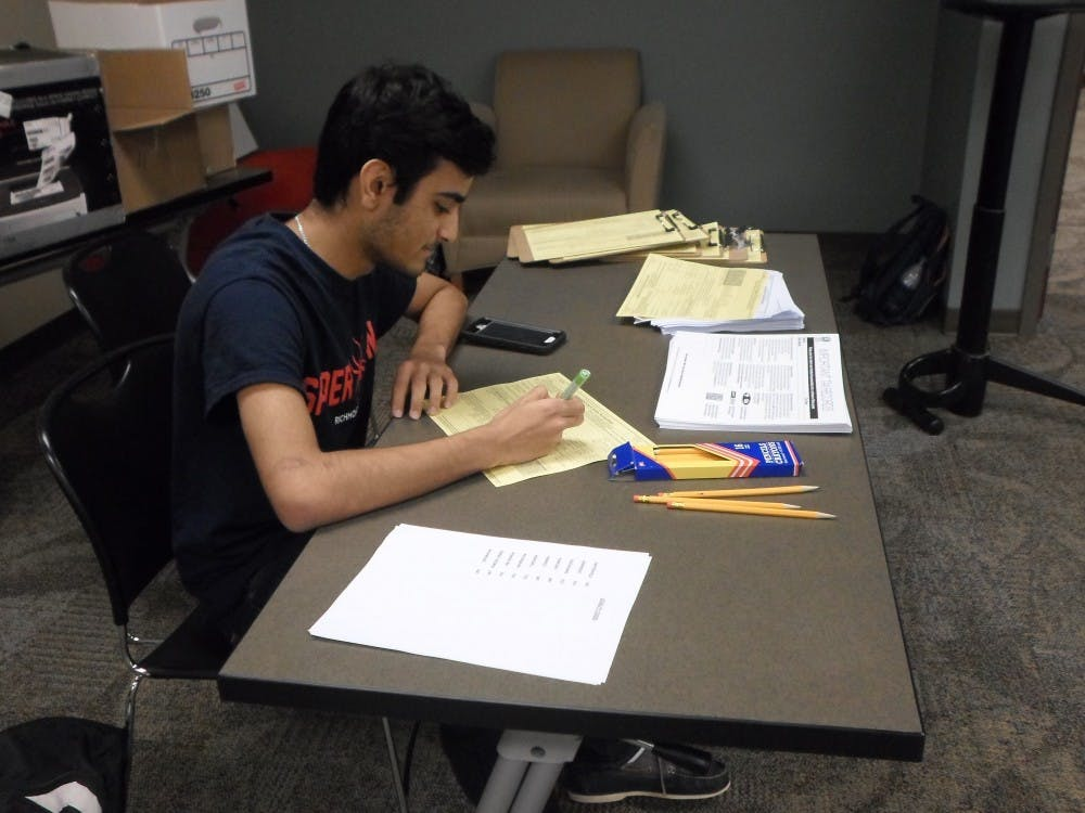 <p>Sophomore Haamid Shaikh looks over a tax return at the VITA center at UR Downtown.</p>