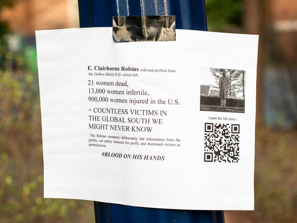 "A flyer taped to a lamp post outside of the Carole Weinstein International Center stating that ""E. [Claiborne] Robins sold and profited from from the Dalkon Shield IUD which left... 21 women dead, 13,000 women infertile, and 900,000 injured."""