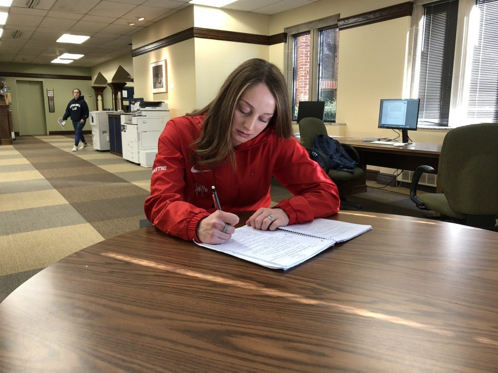 First-year swimmer Jenna Carastro works on homework at Boatwright Memorial Library.