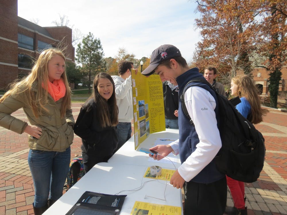 Haley Close, left, and Jacqueline Sinnott, center, discuss how solar power can be implemented on the university campus to students in the forum. Photo by Chase Brightwell.