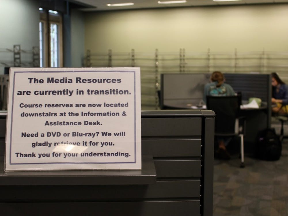 A sign in the MRC directs students to the new temporary location of course reserves and DVDs.