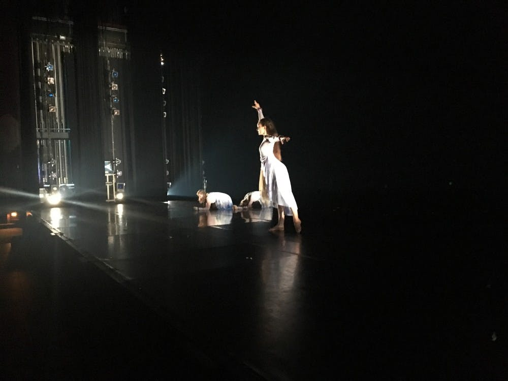 "Karen Fleming (standing), Gianna Dowd and Edie Sanders rehearse senior Cristina Peters's dance, ""Sonámbula,"" as Peters takes notes from the audience."