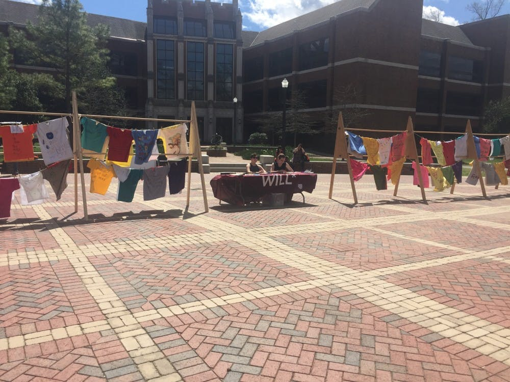 Members of WILL*,Hannah Dunn, WC '19, andKylie Britt, WC '19, sit in between displays of the Clothesline Project.