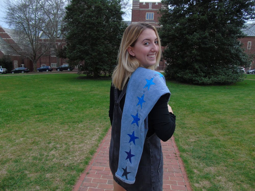 <p>Junior Erin Watton poses with a pair of her custom-painted denim jeans. Watton runs her own business, e.xclusively.&nbsp;</p>